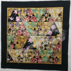 """The smallest of all the quilt tops. It measures in at a whopping 24 1/2"""" square. I was teaching myself how to use modified hexigons and triangles."""